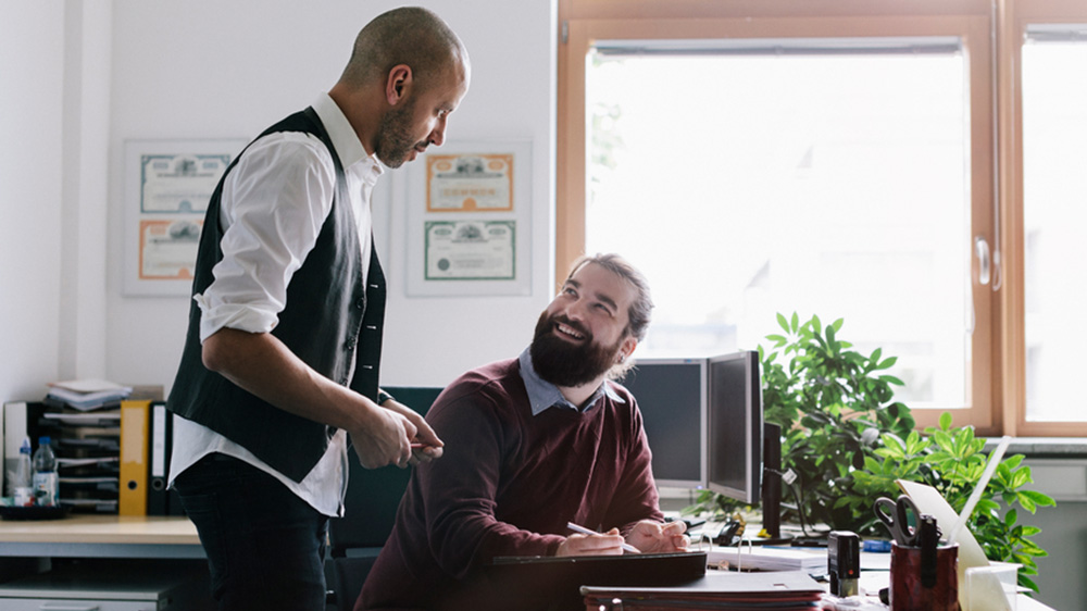 men asking mortgage questions in office
